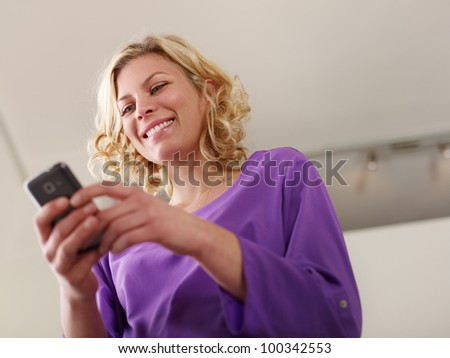 Young beautiful caucasian blonde woman typing e-mail message on smartphone and laughing. Low angle view, copy space - stock photo