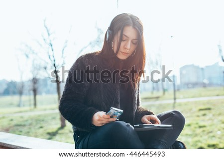 Young beautiful caucasian brown hair woman sitting outdoor in back light listening music with headphones and smart phone hand hold and using tablet - multitasking, technology, music concept - stock photo