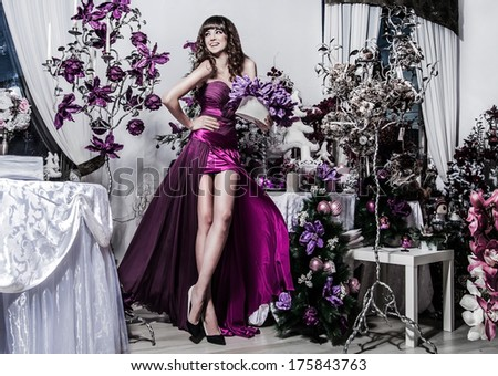 young beautiful caucasian brunette in gorgeous dress, christmas decor - stock photo