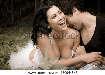 Young beautiful caucasian couple in forest sharing a happy moment - stock photo