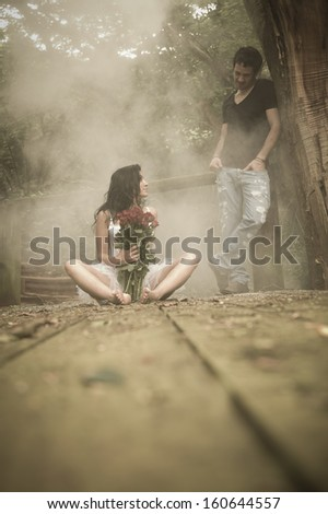 Young beautiful caucasian couple relaxing in forest with bunch of red roses - stock photo
