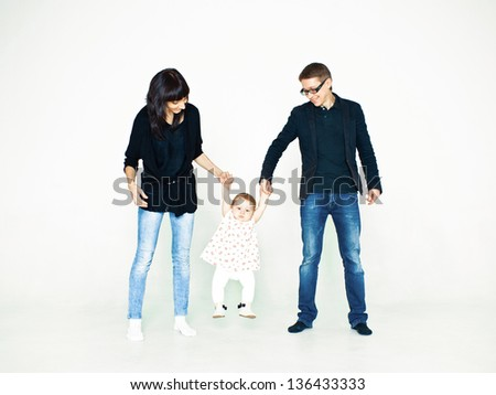 young beautiful caucasian family holding her baby daughter - stock photo