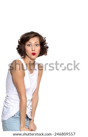 Young beautiful caucasian female brunette model in shirt and jeans shorts posing with expressive emotion, grimacing, exited, shocked, surprised isolated on white - stock photo