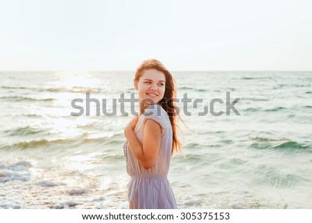 young beautiful caucasian female enjoying the sun on beach during sunrise or sunset - stock photo