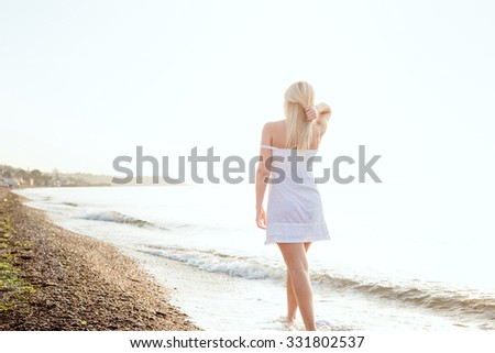 young beautiful caucasian female enjoying the sun on beach during sunrise or sunset - stock photo