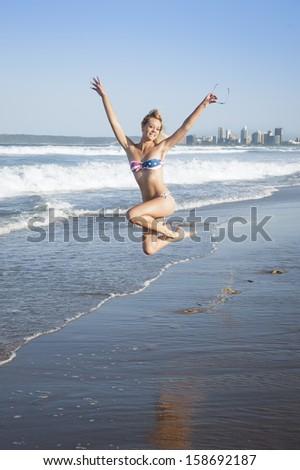 Young beautiful caucasian girl jumping on beach in american flag bikini - stock photo