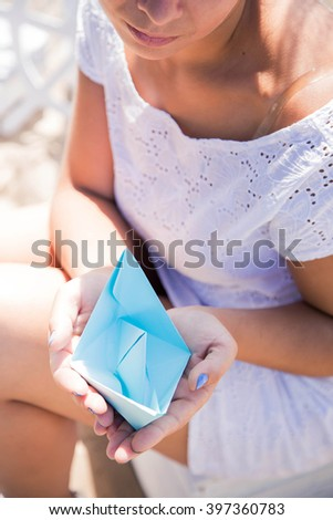 Young beautiful caucasian girl on the river bank in a white dress. Beautiful smile of a young girl. Woman holding blue paper boat. Summer  - stock photo