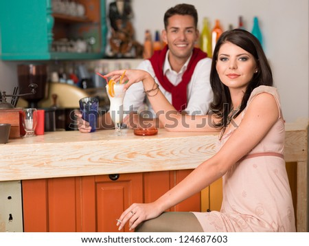 young beautiful caucasian girl sitting at a bar drinking a cocktail an smoking a cigarette with a guy behind the counter - stock photo