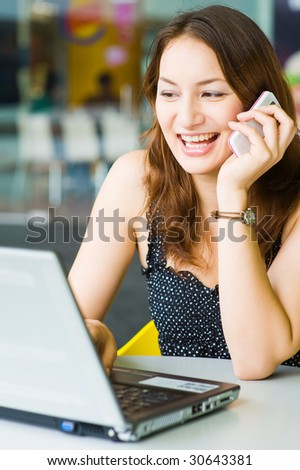 young beautiful caucasian girl talking on phone while using laptop - stock photo