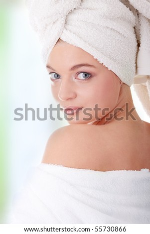 Young beautiful caucasian woman after bath, against abstract green background - stock photo