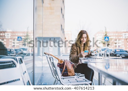 Young beautiful caucasian woman sitting on a bar having a cup of coffee, looking downward and tapping the screen of a smart phone hand hold - break, relax, technology concept - stock photo