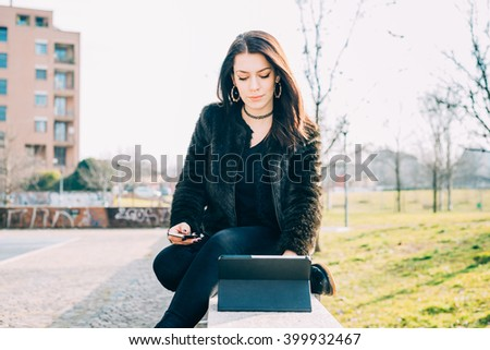 Young beautiful caucasian woman sitting on a small wall using tablet and smart phone handhold, looking downward and tapping the screen - technology, multitasking, communication concept - stock photo