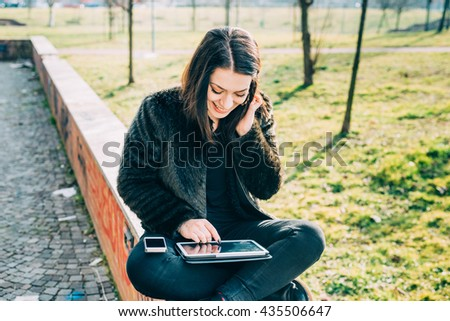Young beautiful caucasian woman sitting on a small wall using tablet on her knee and smart phone, tapping the touchscreen smiling - multitasking, technology, communication concept - stock photo