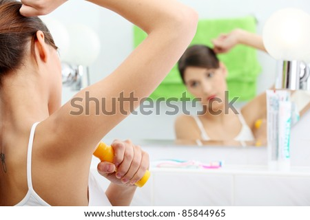 Young beautiful caucasian woman using deodorant at her bathroom - stock photo