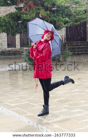 Young  beautiful caucasian woman with an umbrella dressed in Red and  dancing in the rain. - stock photo
