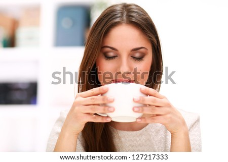 Young beautiful caucasian woman with cup at home - stock photo