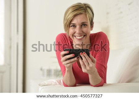 young beautiful Caucasian woman with shorts and modern hair style happy on couch using internet texting on mobile phone app relaxed and cheerful at home living room in communication concept - stock photo