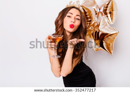 Young beautiful celebrating woman in black dress  flirting  and posing with cocktail in hand and purity balloons . Beautiful model portrait . Bright make up. Attractive girl send a kiss. - stock photo