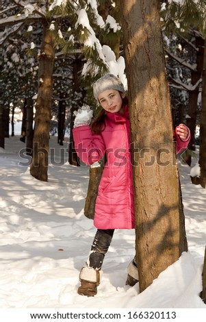 Young beautiful cheerful girl is throwing snowball behind tree  - stock photo