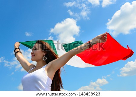 young beautiful cheerful woman holding italian flag against summer blue sky, with love to homeland - stock photo