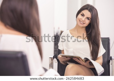 Young beautiful client with long straight brunette hair reading magazine in hairdressing salon. - stock photo