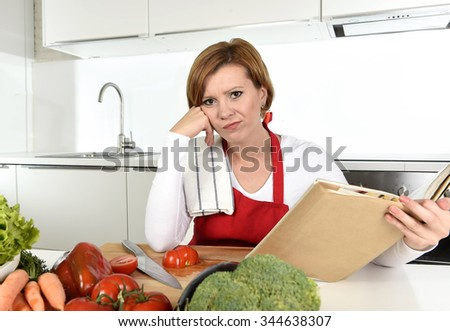 young beautiful cook woman bored and confused wearing red apron sitting at home kitchen reading recipes book bored and confused in domestic stress and lifestyle concept - stock photo