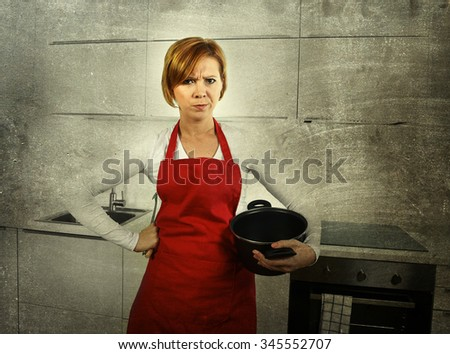young beautiful cook woman confused and frustrated face expression wearing red apron holding cooking pot at home kitchen in domestic stress and lifestyle concept grunge dirty background edit - stock photo