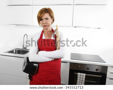 young beautiful cook woman in angry upset and frustrated face expression with folded arms wearing red apron holding cooking pot at home kitchen in domestic stress and lifestyle concept - stock photo