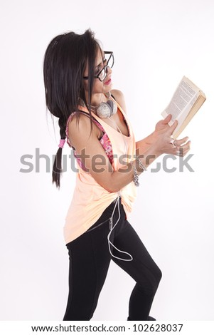 Young beautiful cool woman with headphones reading a book. - stock photo