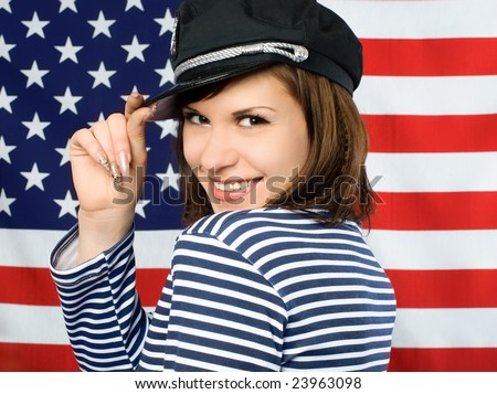young beautiful coquettish sailor standing near the American flag and smiling - stock photo