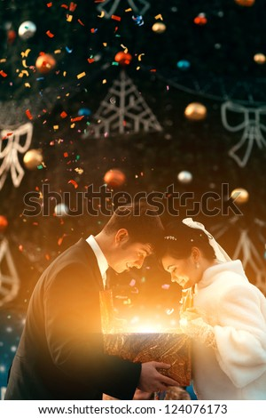 Young beautiful couple are holding a magic Christmas gift - stock photo