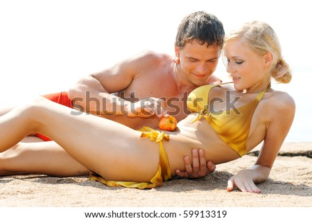 Young beautiful couple are holding on the beach - stock photo