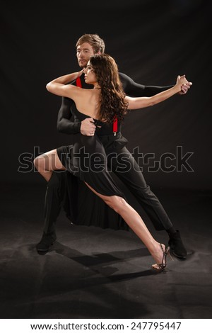 Young beautiful couple dancing the sultry tango against black backdrop - stock photo