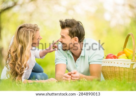 Young beautiful couple dressed casual lying on the lawn in summer park. - stock photo
