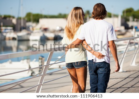 Young beautiful couple enjoying a walk by the harbor - stock photo