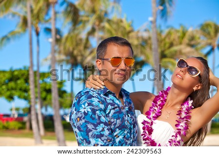 Young beautiful couple enjoying beach getaway. Couple in love, summer luxury vacation in Hawaii. Travel holidays concept. - stock photo