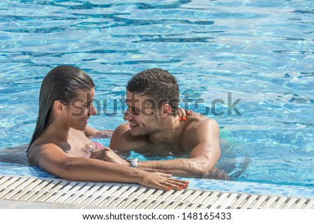 Young beautiful couple enjoying in pool on hot summer day  - stock photo
