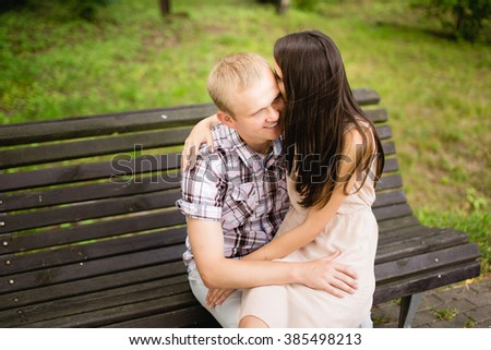 Young beautiful couple in love sitting together and hugging on the bench outdoors - stock photo