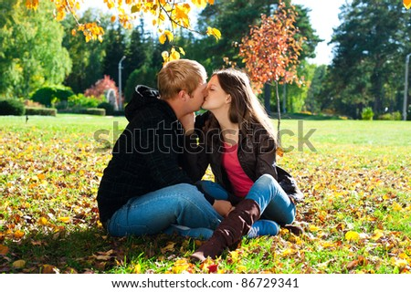 Young beautiful couple kissing in autumn park - stock photo