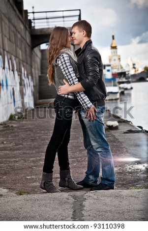 Young beautiful couple kissing on riverside - stock photo