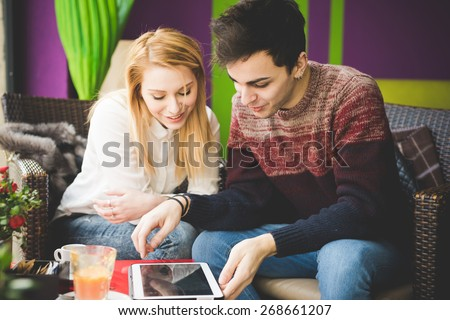 young beautiful couple lovers sitting at the bar using wireless tablet connected online - stock photo