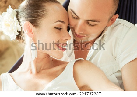 Young beautiful couple lying in a hammock and enjoy each other - stock photo