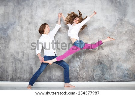 young beautiful couple of dancers posing on studio background - stock photo