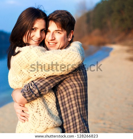 Young beautiful couple outdoor fashion portrait. Attractive boy and girl posing and having fun on a beach in sunny cold weather. - stock photo
