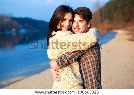 Young beautiful couple outdoor sensual portrait. Handsome man and pretty woman having fun on the beach - stock photo
