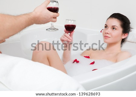Young beautiful couple taking a bath with a glass of red wine - stock photo