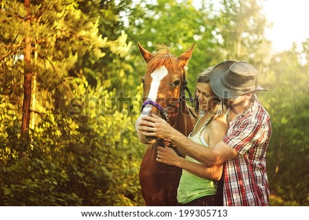 Young beautiful couple  with a horse at sunset. - stock photo