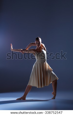 Young beautiful dancer in beige dress dancing on gray studio background - stock photo