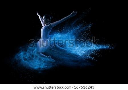 Young beautiful dancer jumping into blue powder cloud  - stock photo