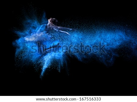 Young beautiful dancer jumping into blue powder cloud  - stock photo